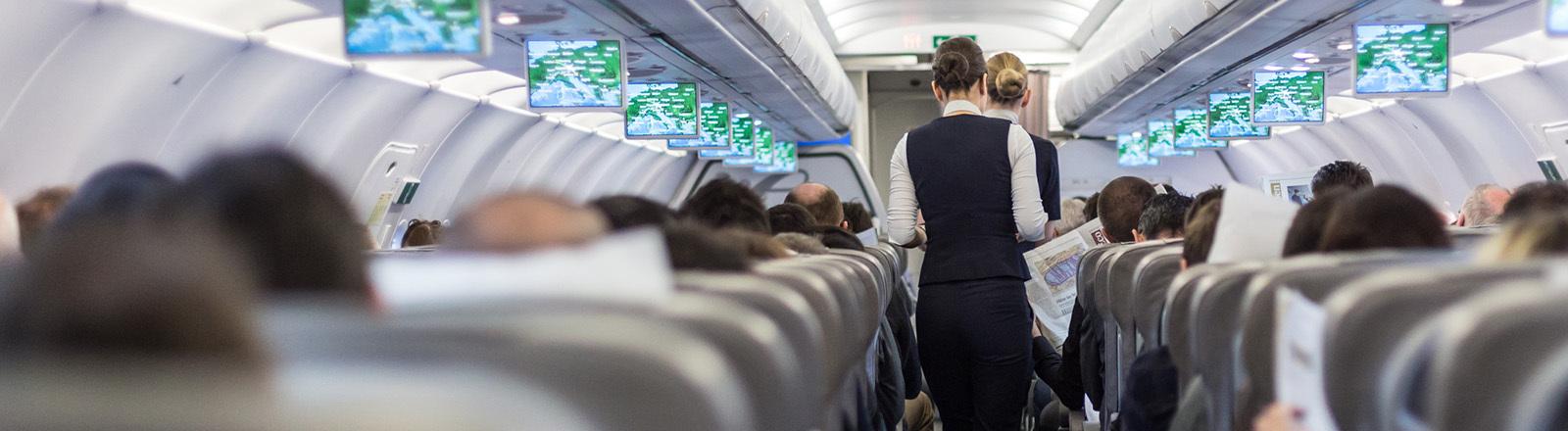 Innenraum eines Verkehrsflugzeuges mit Stewardess, die die Passagiere während des Fluges auf den Sitzen bedient. von kastoimages