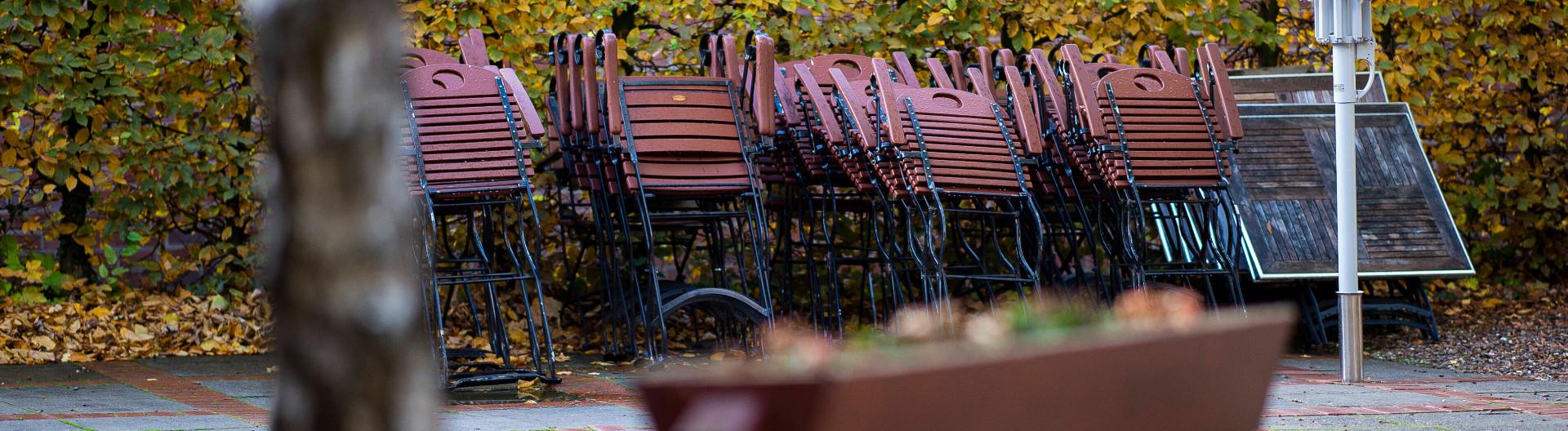 Leere und zusammengestellte Tische und Stühle im Außenbereich eines Restaurants