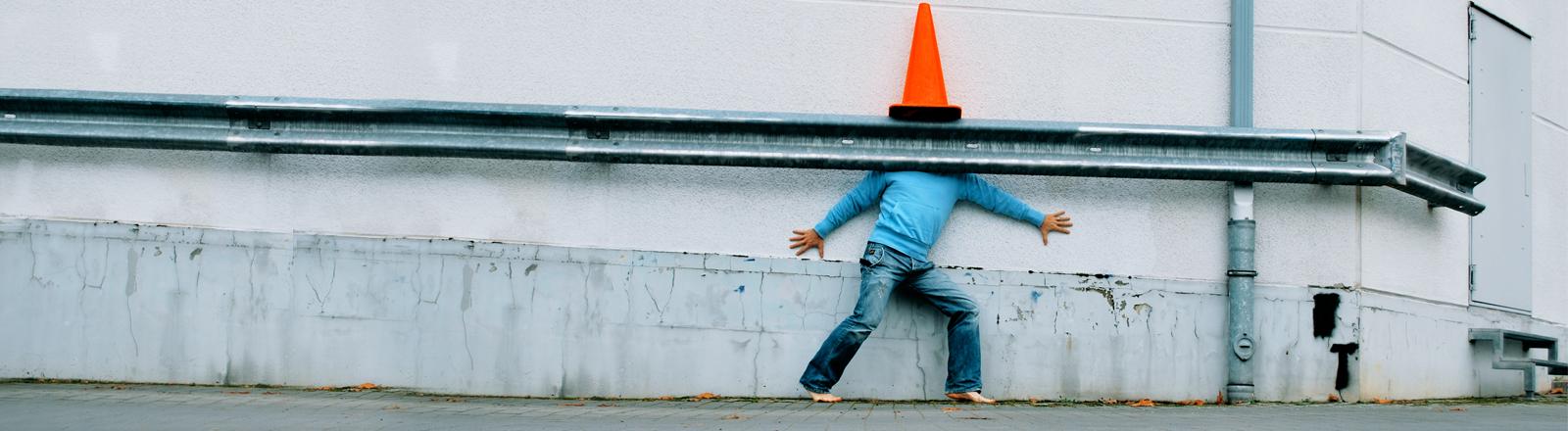 Ein Mann versteckt sich hinter einer Leitplanke, statt einem Kopf sieht man eine orange Pylone