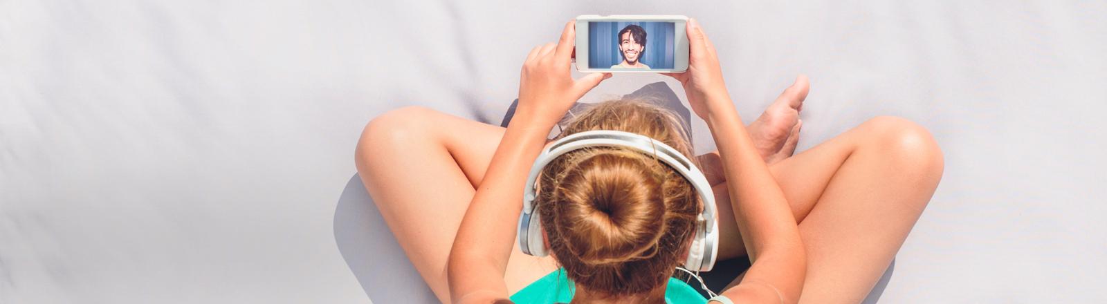 Ein Mädchen sitzt vor einem Smartphone, darauf ein Bild von einem jungen Mann