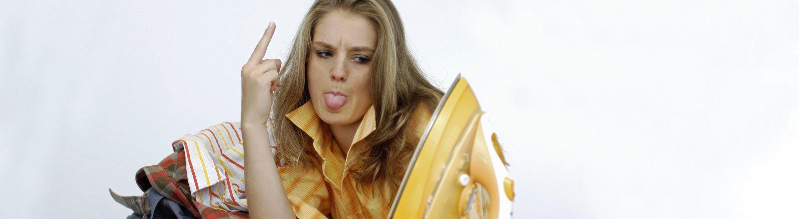 Frau lehnt sich auf Bügelbrett, streckt Zunge raus und zeigt den Mittelfinger