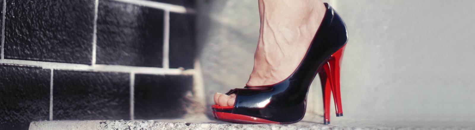 Fuß in schwarz-roten hochhackigen Pumps auf Treppenabsatz