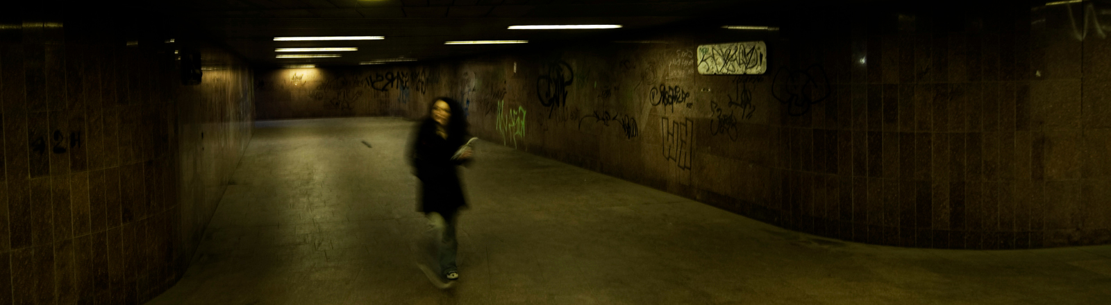 Eine junge Frau schaut in einer U-Bahn-Station auf ihr Mobiltelefon