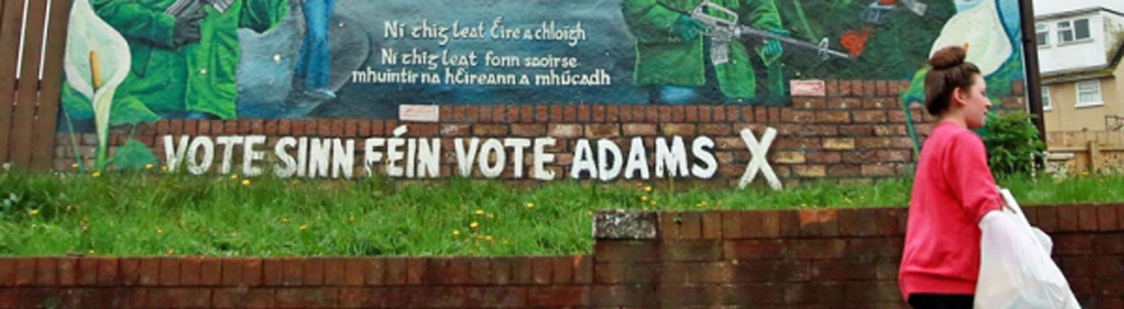 Eine Frau geht in Belfast an einer Wahlwerbung der Partei Sinn Fein vorbei.