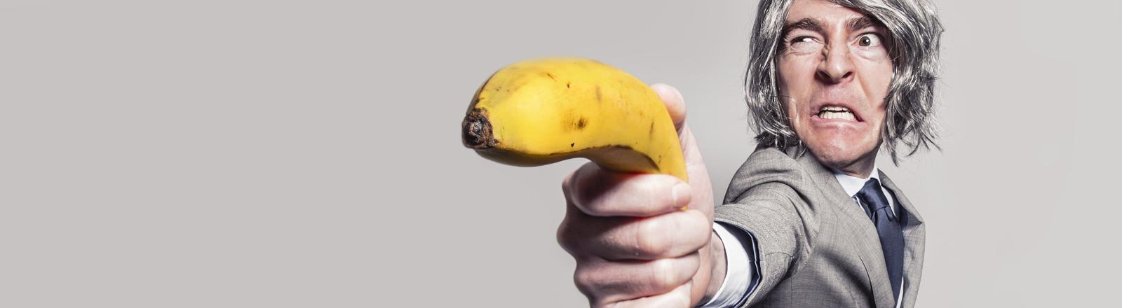 Mann hält Banane wie eine Pistole in der Hand