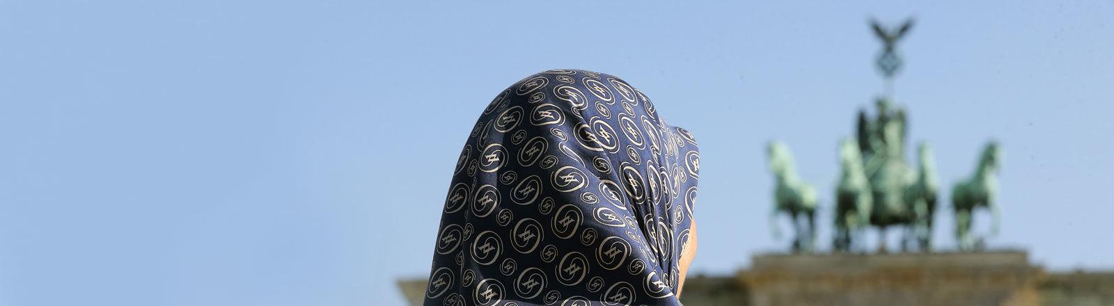Eine muslimische Frau mit Kopftuch steht am 27.09.2016 vor dem Brandenburger Tor in Berlin