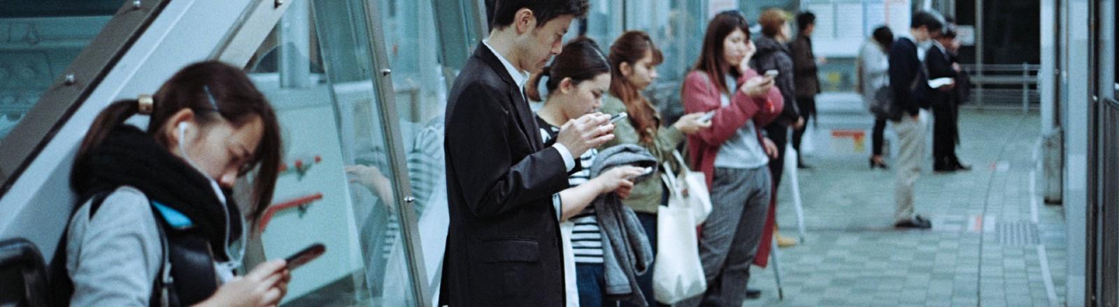 Menschen warten und schauen auf Smartphone