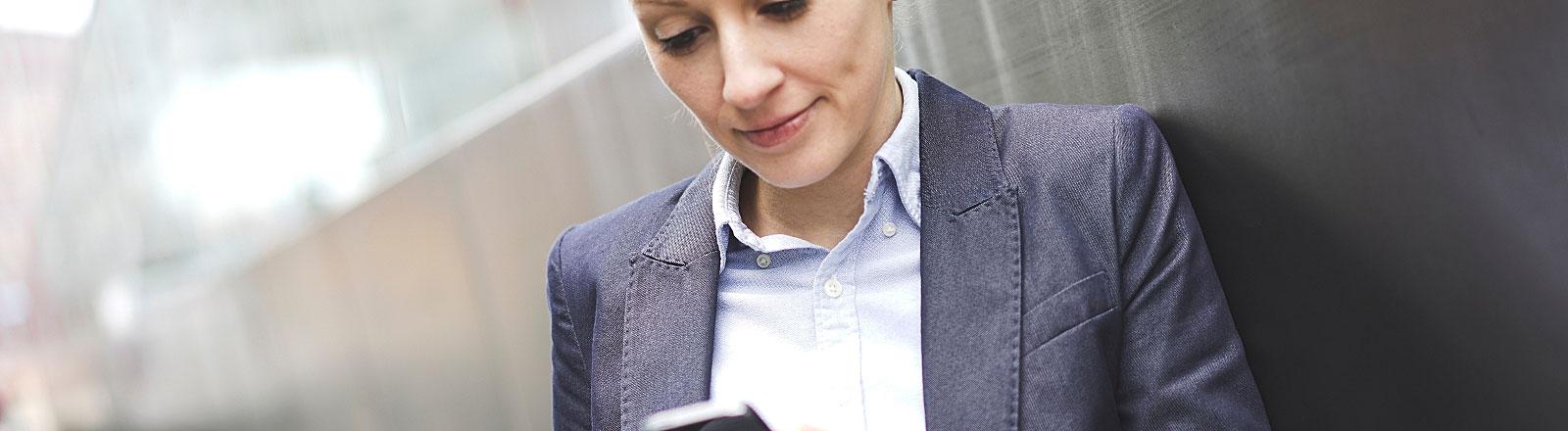 Frau mit Smartphone lehnt an einer Wand
