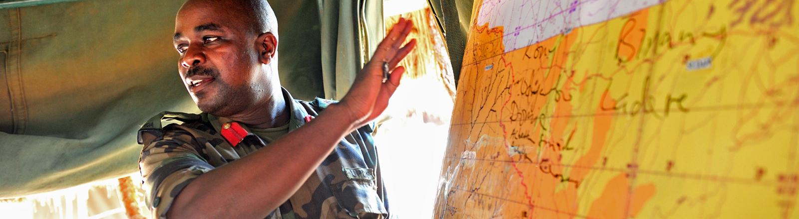 Ein General steht an einer Karte des Einsatzgebietes. Soldaten der ugandischen Armee (UPDF) patrouillieren durch den Dschungel der Republik Zentralafrika auf der Suche nach dem Rebellenführer Joseph Kony.