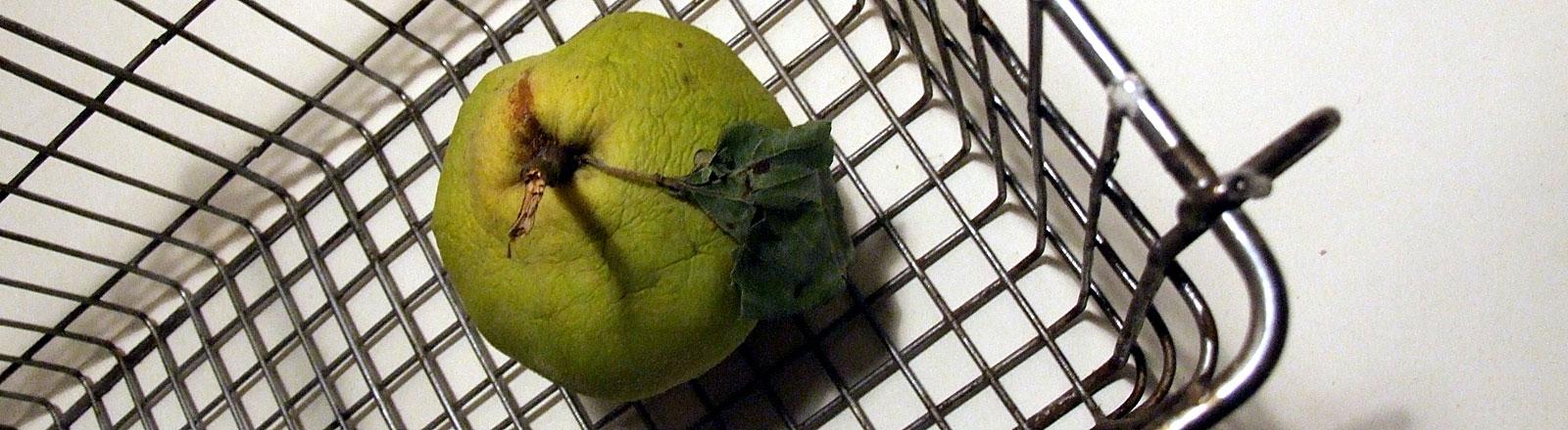 Alter Apfel im Supermarkt-Korb