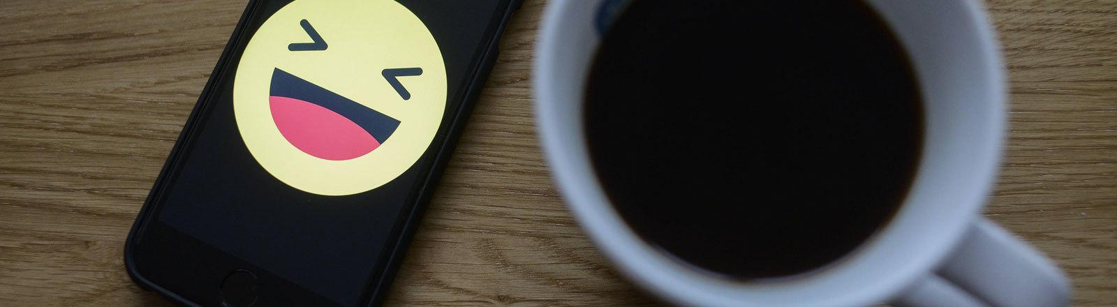 Lachen-Emoji auf Smartphonecover neben Kaffeetasse