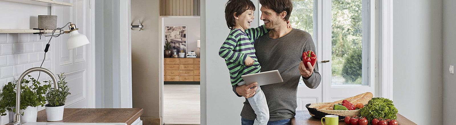 Mann mit Sohn auf dem Arm und Paprika in der Hand in moderner Küche