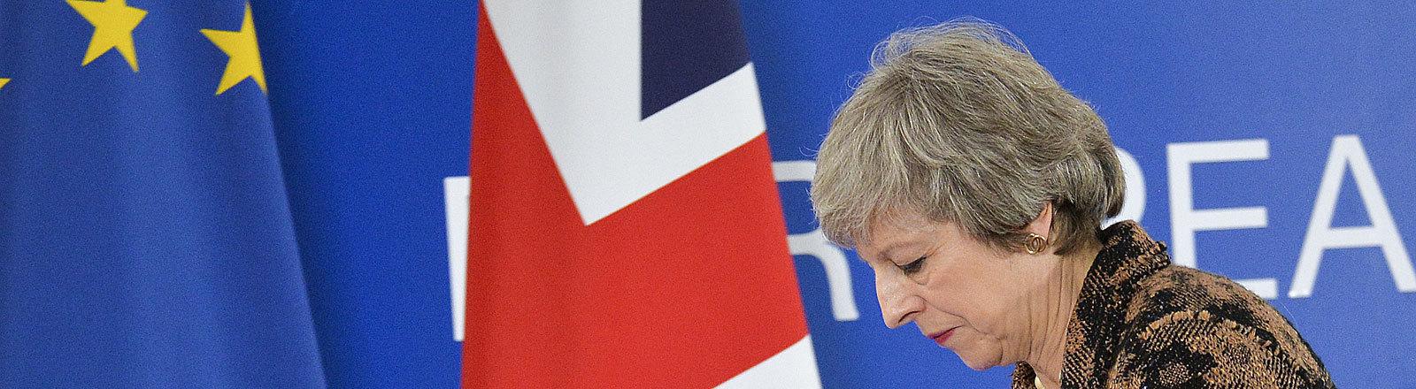 Theresa May blickt deprimiert und läuft an der britischen und europäischen Flagge vorbei