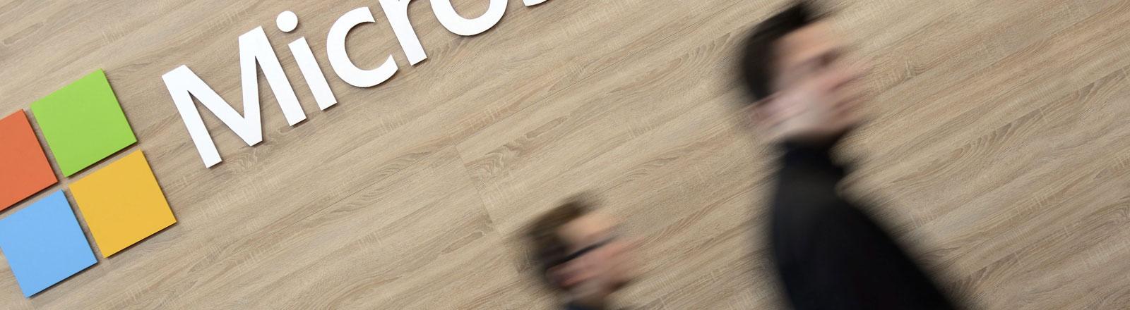 Zwei Männer gehen am Microsoft-Logo vorbei