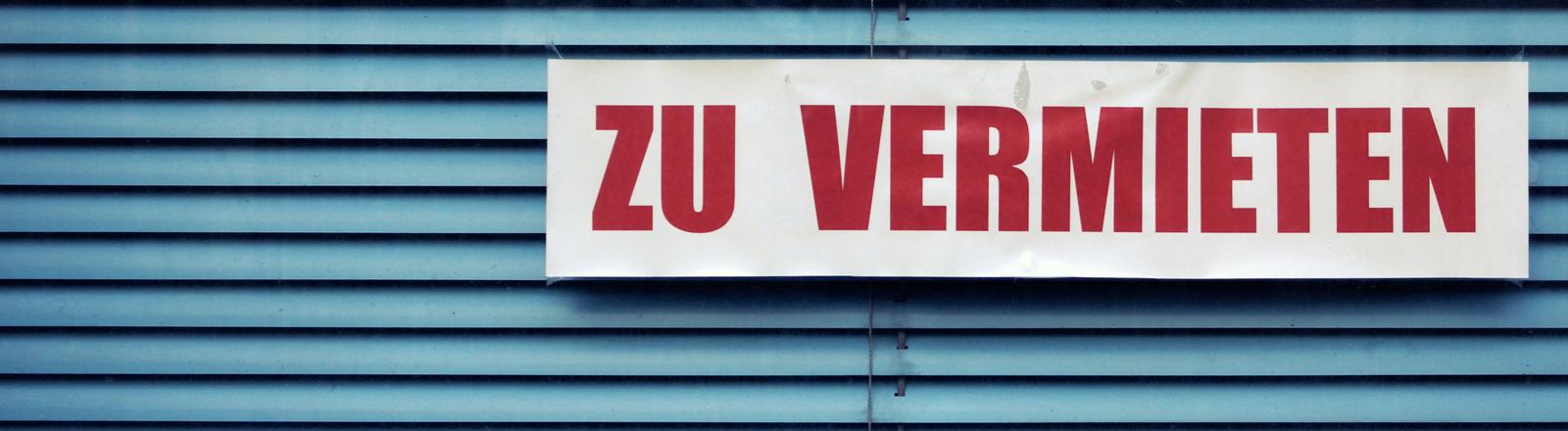 Auf einer Jalousie ist ein Schild angebracht: Zu Vermieten