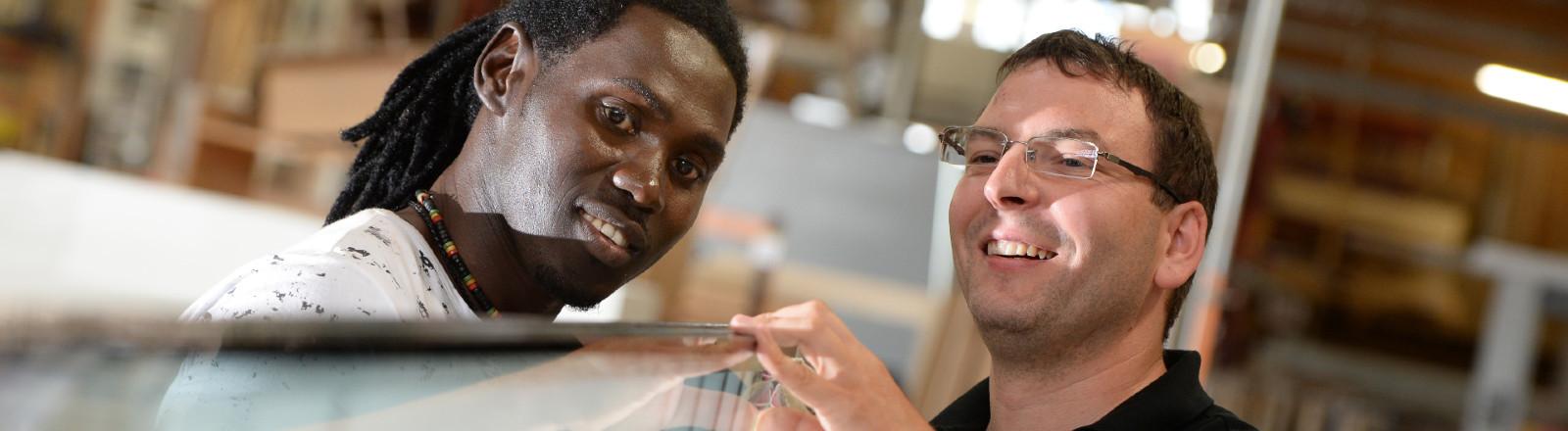 Asylbewerber Omar Ceesay (l) und Geschäftsführer Alexander Lanz unterhalten sich am 27.08.2015 in der Schreinerei Holitsch in Tettnang-Hiltensweiler (Baden-Württemberg) an einer Glasscheibe, die in eine Tür eingesetzt wird. Schreiner Omar Ceesay kam aus Libyen über Italien nach Deutschland.