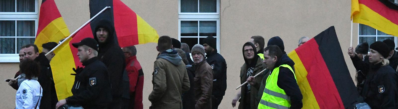 """10.11.2018, Mecklenburg-Vorpommern, Greifswald: Anhänger der Partei Alternative für Deutschland (AfD) laufen bei ihrer Demonstration unter dem Motto """"Nein zum globalen Migrationspakt"""" durch die Altstadt."""