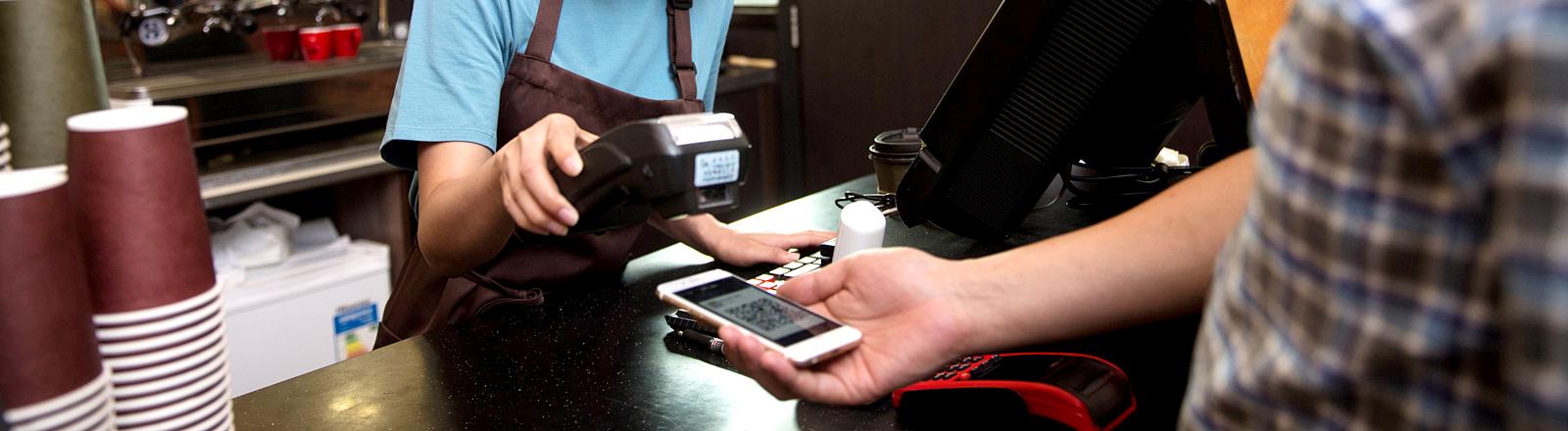 Mann bezahlt mit Smartphone an einer Kasse.