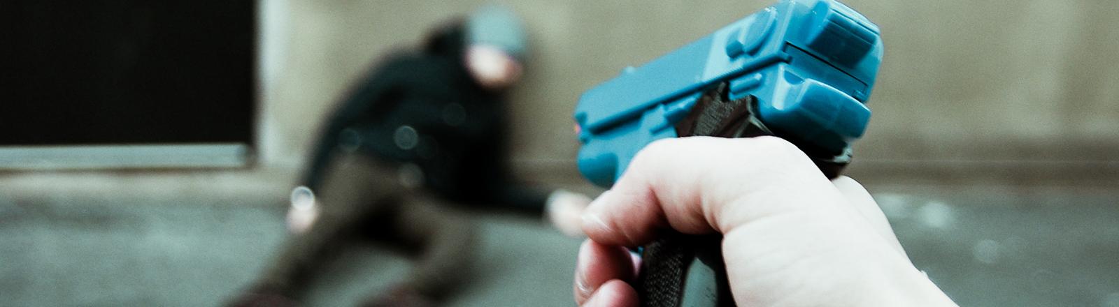 Mann oder Frau zielt mit Pistole auf einen Mann