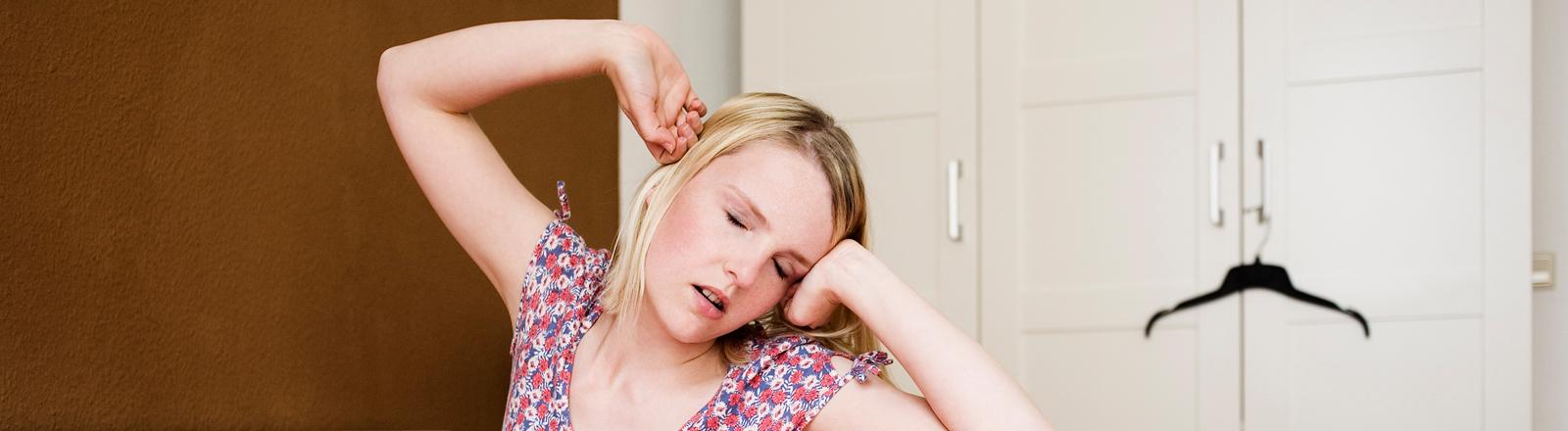 Eine junge Frau sitzt auf einem Bett und gähnt.