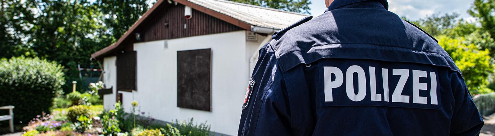 06.06.2020, Nordrhein-Westfalen, Münster: Bei den Ermittlungen nach schwerem sexuellem Missbrauch von Kindern steht ein Polizeibeamter vor der Gartenlaube, wo der vermutliche Haupttäter Teile seiner Server-Anlage unterbrachte.