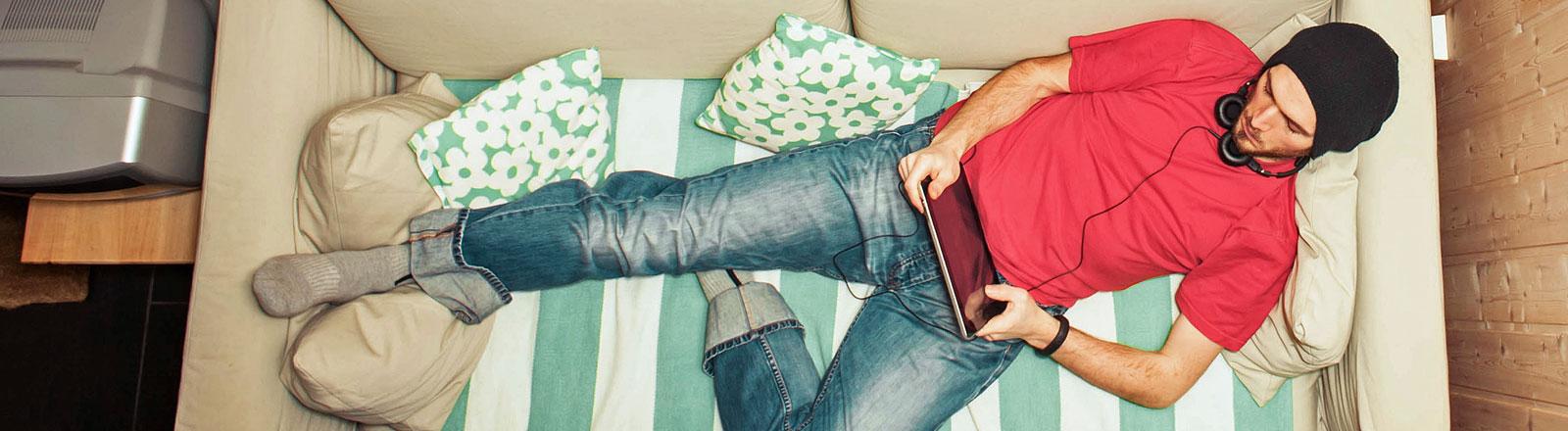 Junger Mann mit Kopfhörern und Tablet auf dem Sofa