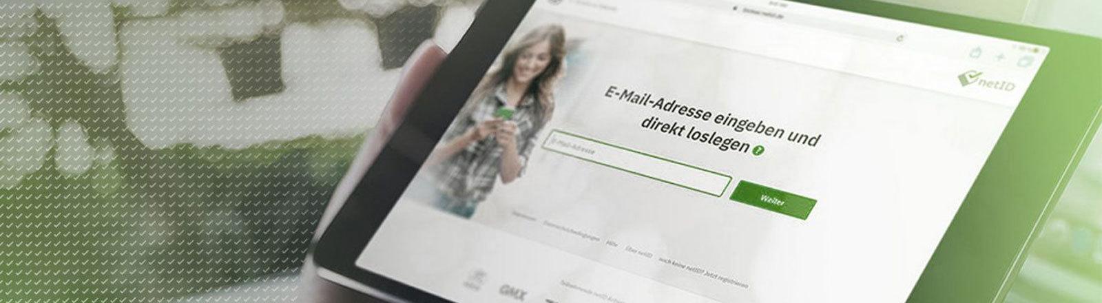 Mann hält Pad mit Website netid.de in der Hand