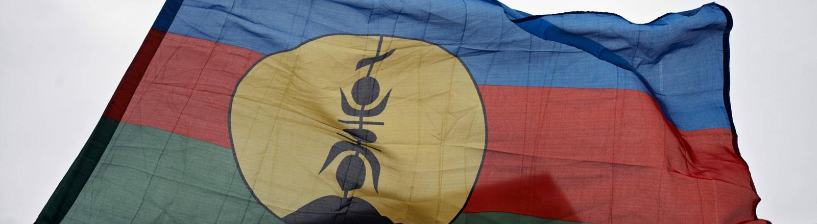 Die blau-rot-grün gestreifte Flagge von Neukaledonien mit einem gelben Symbol in der Mitte weht vor einem Haus in Tolouse, Frankreich.