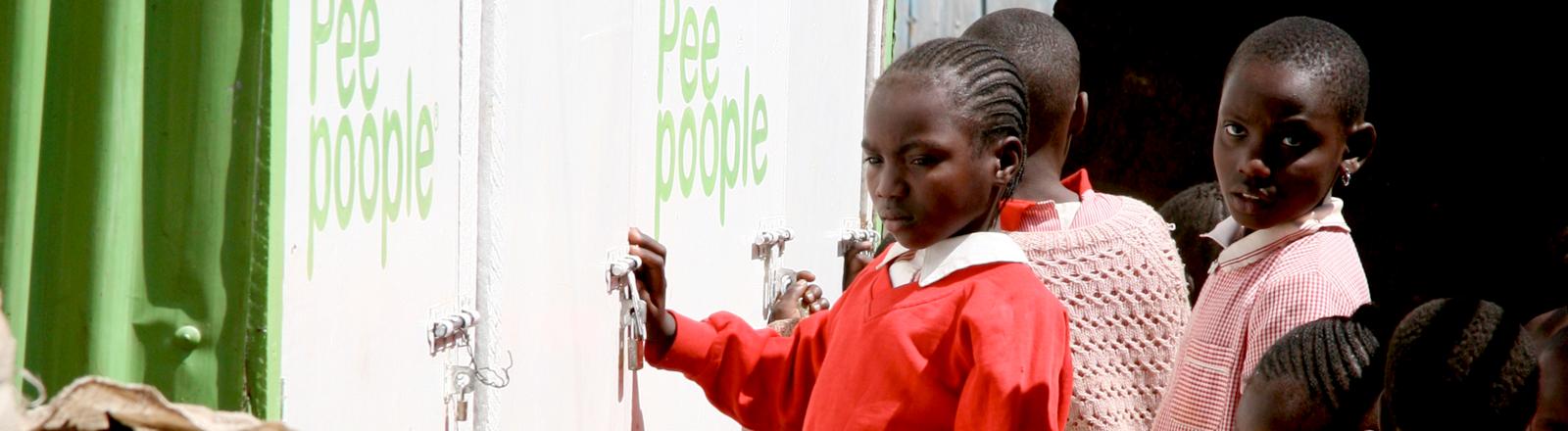 Mädchen in Kenia stehen vor einem Peepoople-Schulklo an