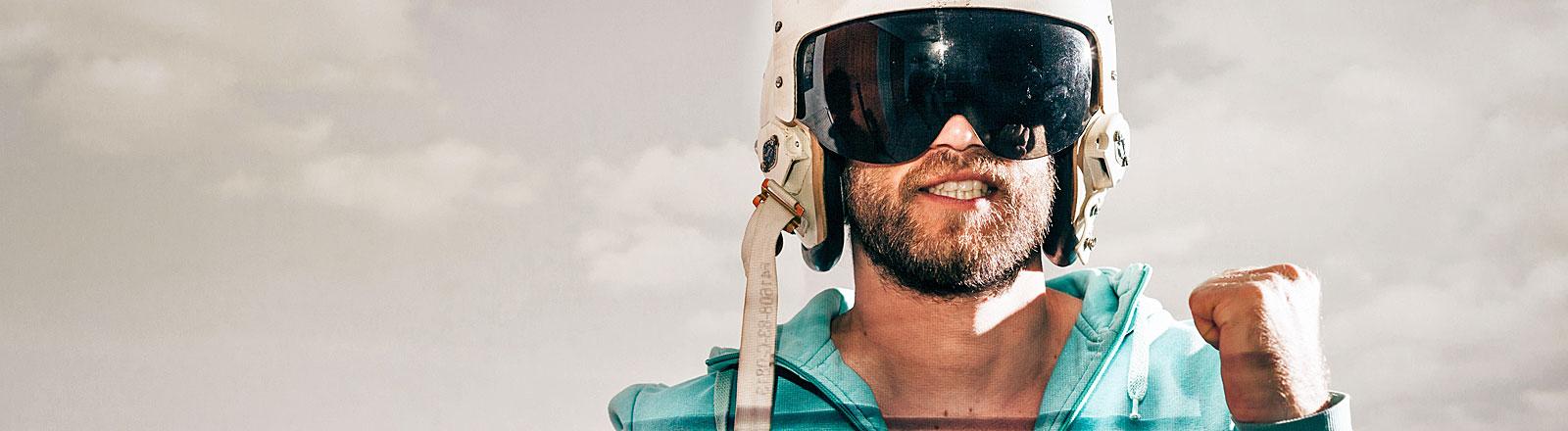 Mann mit Helm und Sonnebrille, die Haust ballend