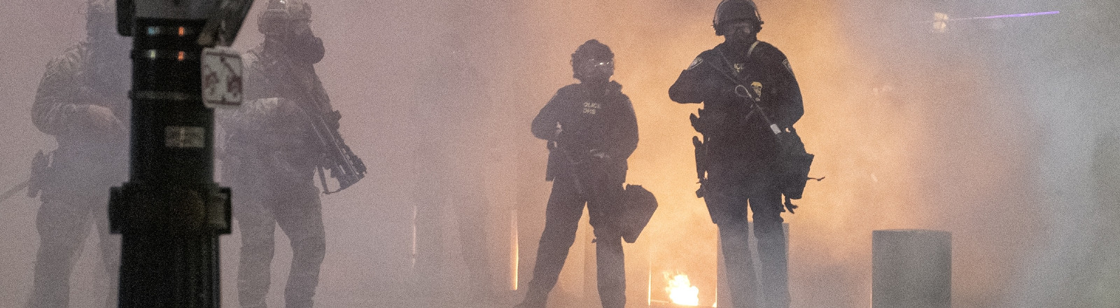 21.07.2020, USA, Portland: 6291910 21.07.2020 Federal law enforcement are seen standing next to an open flame through CS gas during the 54th day of protesting against police brutality and racial inequality in Portland, the United States.