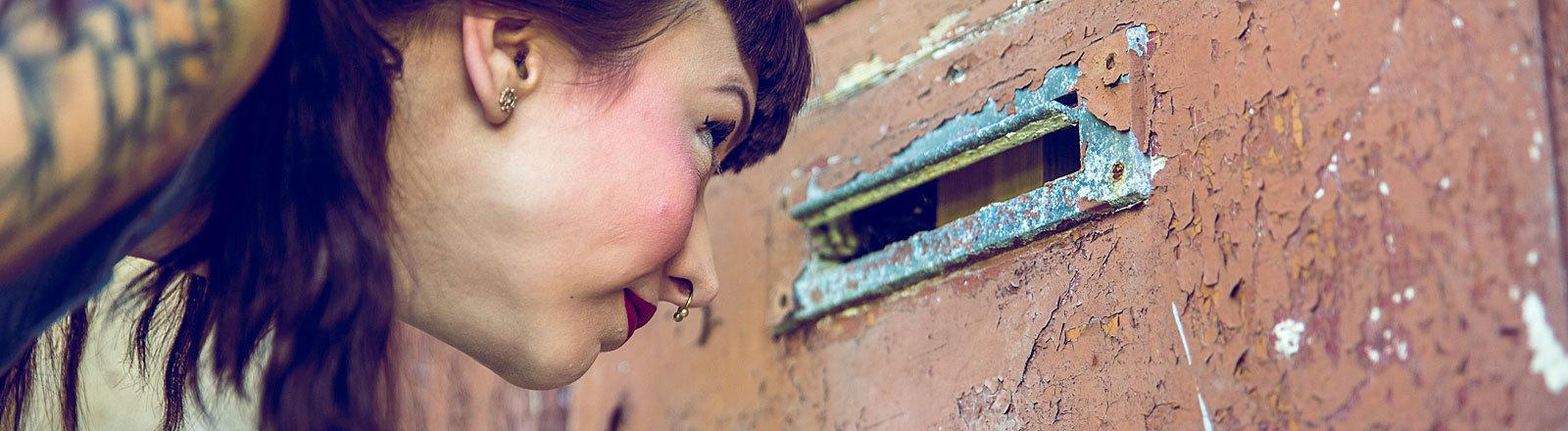 Frau schaut durch offenen Briefkastenschlitz