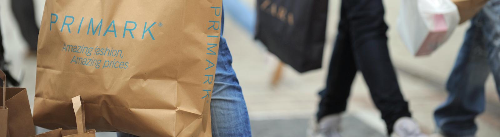Ein junger Mann hält eine gefüllte Einkaufstüte des Textildiscounter Primark aus der Republik Irland auf der Zeil in Frankfurt am Main in den Händen.