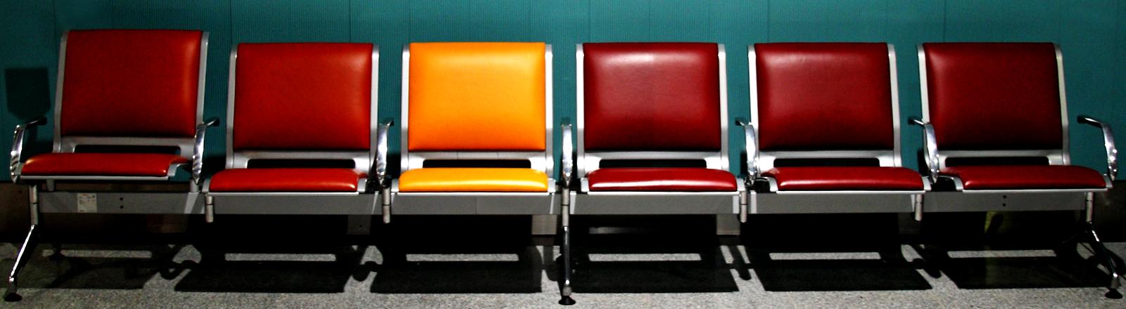 Eine Reihe roter Stühle, dazwischen ein oranger