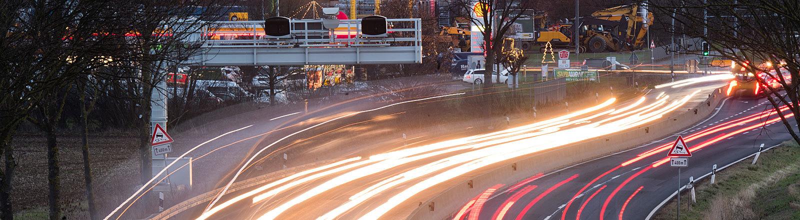 Niedersachsen, Laatzen: Autos fahren auf der Bundesstraße B6 in der Region Hannover vorbei an einem Streckenradar (Aufnahme mit langer Verschlusszeit)