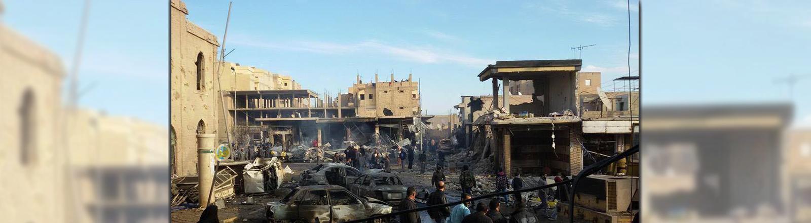 Eine komplett zerstörte Straße in Rakka, zwischen den Trümmern und verkohlten Autos laufen Menschen.