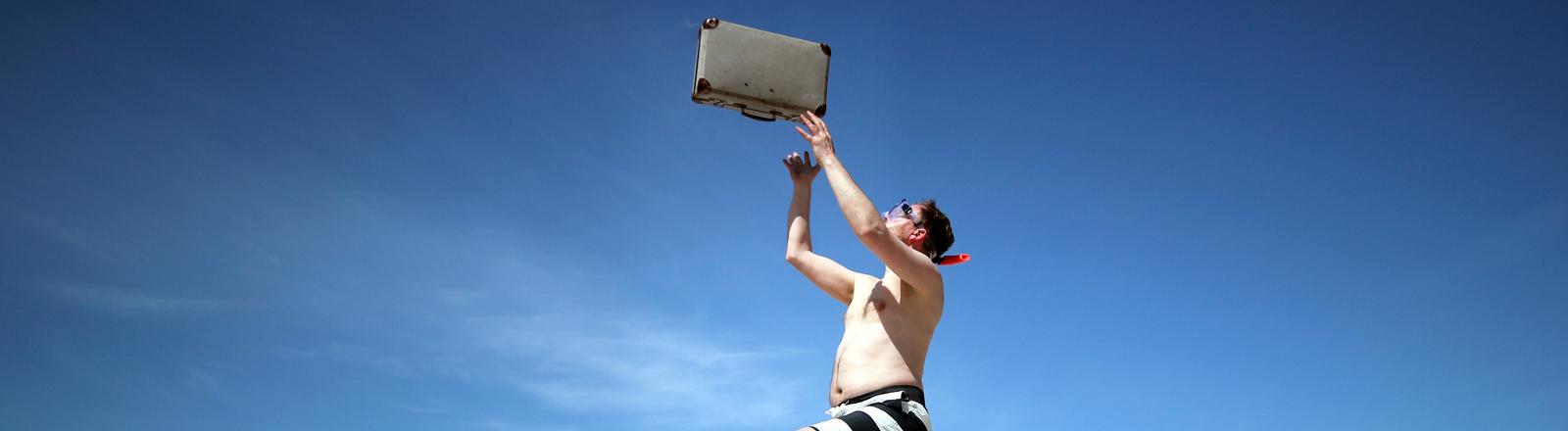 Ein Mann in Badehose wirft einen Koffer in die Luft