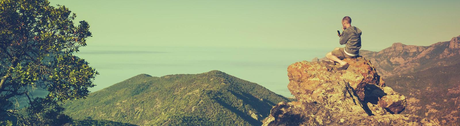 Ein junger Mann auf einem Berg arbeitet mit seinem Handy