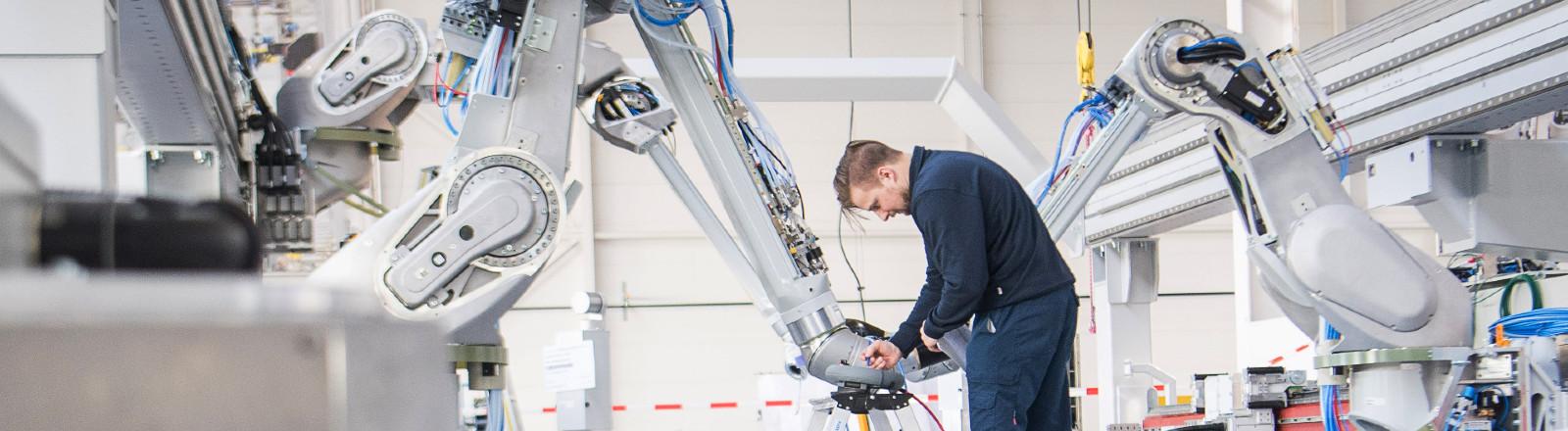 Baden-Württemberg, Bietigheim-Bissingen: Ein Mitarbeiter testet einen Lackierroboter bei der Dürr AG.