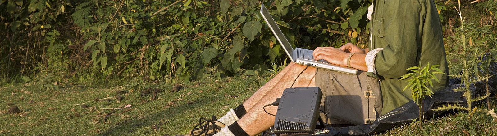 Student mit Laptop und Sateltten-Internetverbindung in Afrika