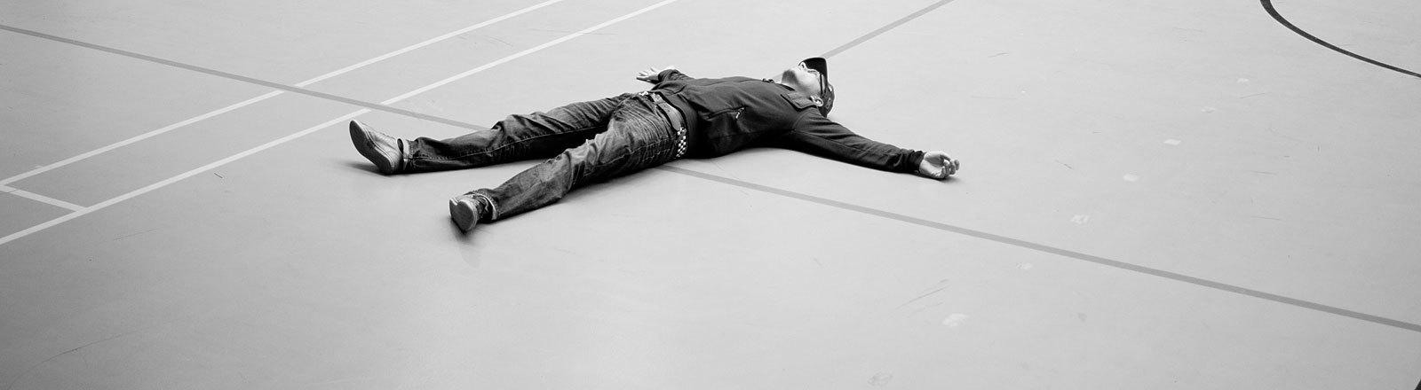 Mann liegt schlafend auf Sporthallen-Boden