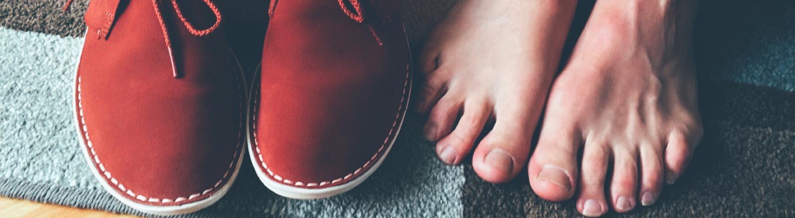 Ein paar Füße neben ein Paar Schuhen