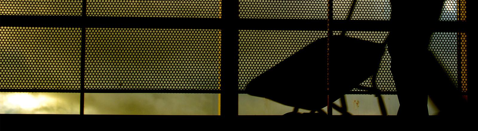 Ein Mensch mit Schubkarre im Gegenlicht