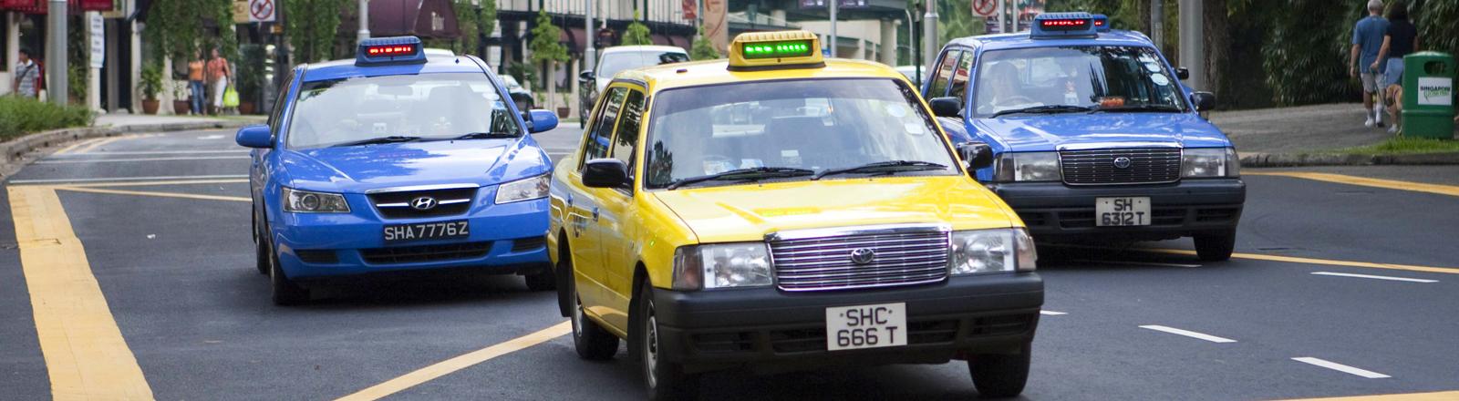 ein gelbes und zwei blaue Taxis in Singapur