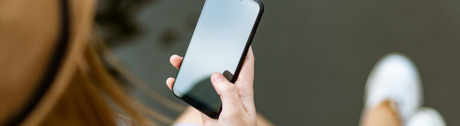 Eine junge Frau schaut auf ihr Smartphone