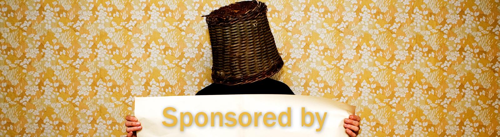 Ein Mann hat einen Papierkorb auf dem Kopf und hält eine Papierrolle auf der sponsored by steht