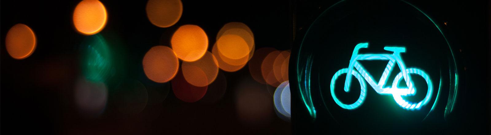Eine grüne Fahrradampel im Dunkeln
