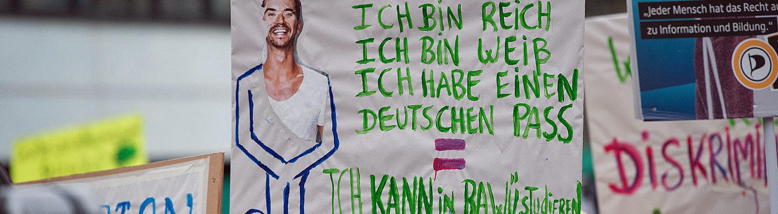 """Ein Demonstrant hält ein Schild mit der Aufschrift """"Ich bin jung, ich bin reich, ich bin weiß, ich habe einen deutschen Pass = Ich kann in Ba-Wü studieren"""" hoch"""