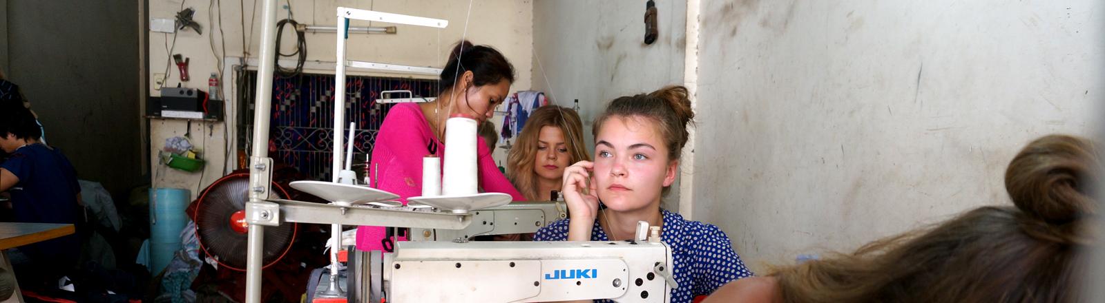 Frida sitzt in Kambodscha an einer Nähmaschine