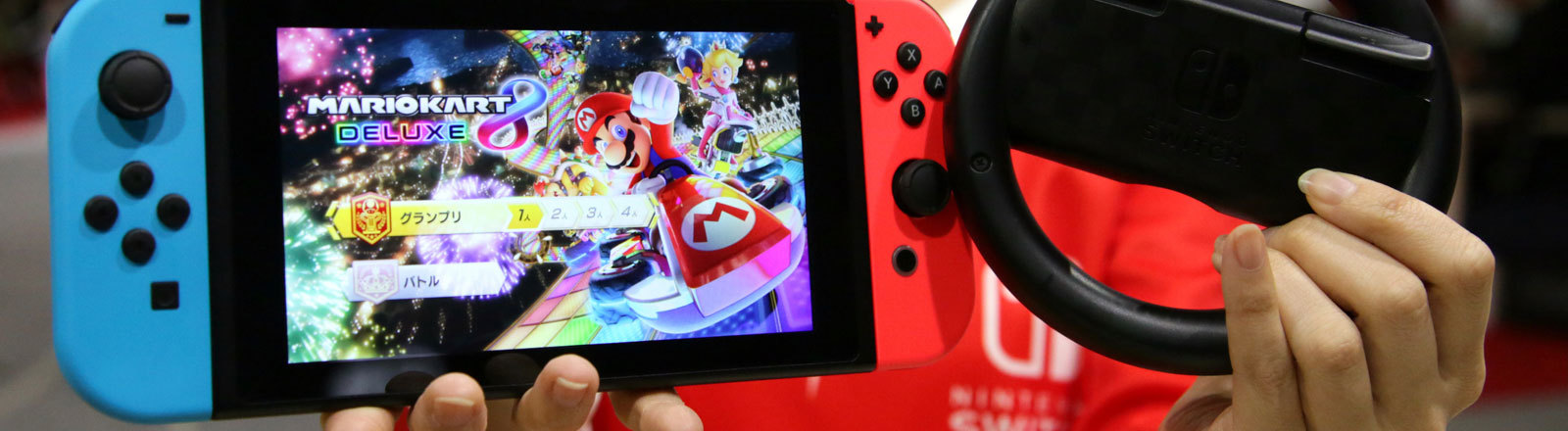 Asiatin hält Switch Konsole mit Super Mario Game und Lenkrad in die Kamera